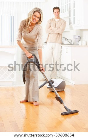 House work, vacuum cleaner, young couple, home, kitchen. Housework - stock photo