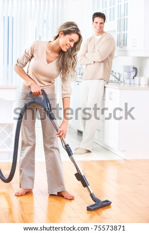 House work vacuum cleaner young couple home kitchen. Housework