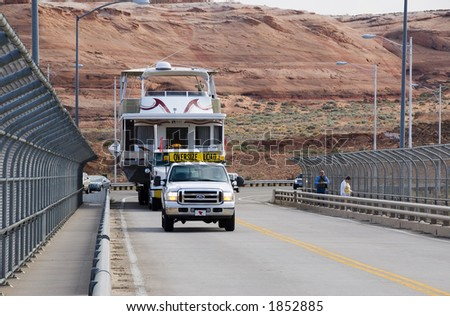 Houseboat being transported across the bridge at Glen Canyon Dam - stock photo