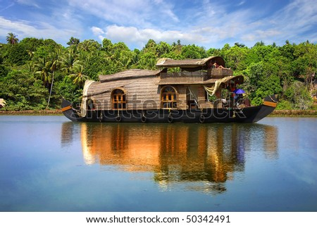 Houseboat in backwaters on a background of the palm tree plantation - stock photo