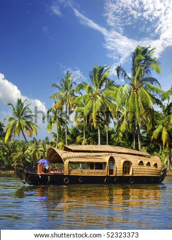 Houseboat in backwaters on a background of the palm tree plantation