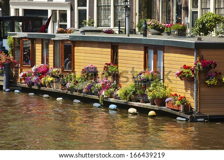 Houseboat with flowers in Amsterdam, The Netherlands,  - stock photo