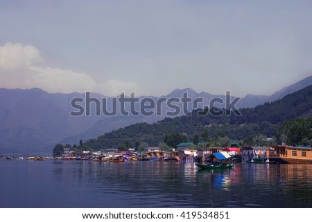 Houseboats on the lake in Srinagar against the mountains. India - stock photo