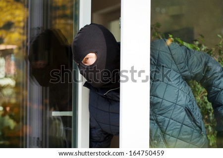 Housebreaker wearing a mask looking through the window - stock photo