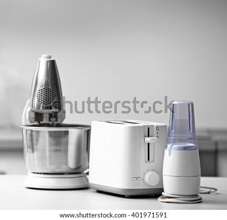 Household and kitchen appliances on the table in kitchen - stock photo
