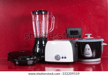 Household appliances in modern kitchen red background  - stock photo