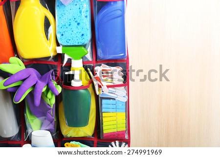 Household chemicals in holder hanging on wooden door, closeup - stock photo