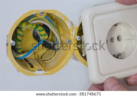 Household electrical box for connecting an electrical outlet in a residential building in a white unpainted wall of yellow color with wires during the working process connection - stock photo