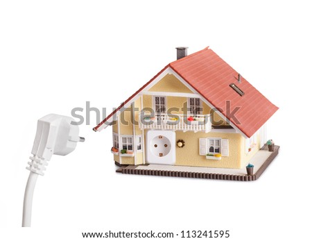Household power and energy concept with an electrical plug and a model house with the corresponding socket in its exterior wall