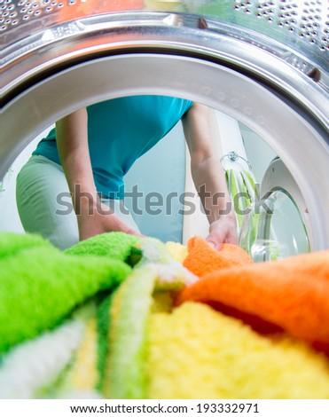 householder woman loading clothing into washing machine - stock photo