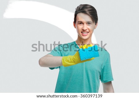 Housekeeping concept. Studio portrait of handsome young man in gloves cleaning glass with wisp. Isolated on white. - stock photo