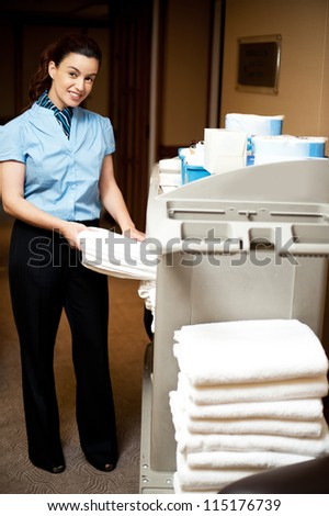 Housekeeping in charge pulling out the bath towel from the cart to deliver it to rooms - stock photo