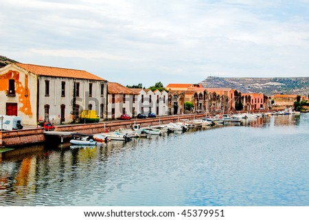 Houses along the coast with reflection in bosa, sardegna - stock photo