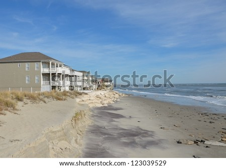 Houses along the shore protected by sandbags - stock photo