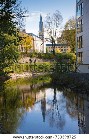 Houses and a Church by the river, trees in the fall on the bank of the river, blue sky and reflection in water