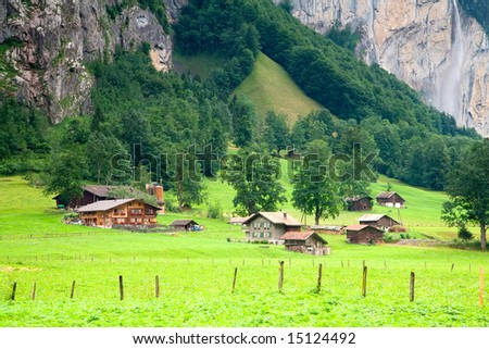Houses and Barns close to a Steep Rocky Mountain in Switzerland - stock photo