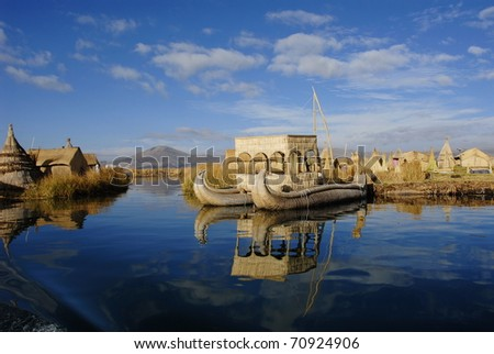 Houses and boats on the floating islands - stock photo