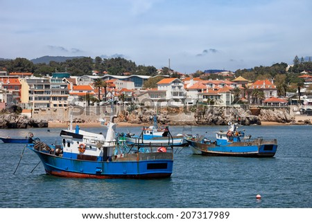 Houses and fishing boats moored at bay in resort town of Cascais, Portugal. - stock photo
