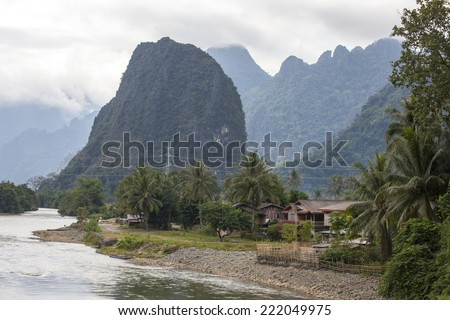 Houses and mountains are located along the coast Nam song river Vang Vieng,Laos. - stock photo