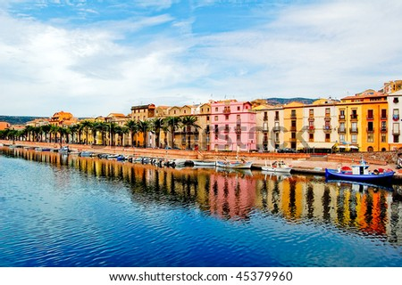 Houses and palm trees along the coast with reflection in bosa, sardegna - stock photo