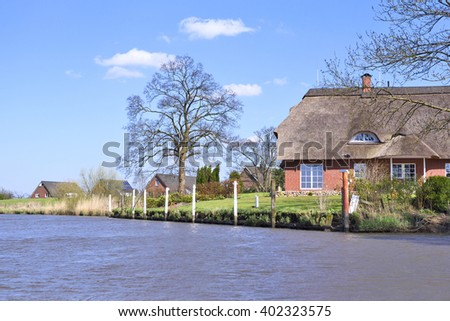 Houses at a riverside. Toned image with farm houses in the dusk or evening sun. Sunset at a river in North Germany. - stock photo