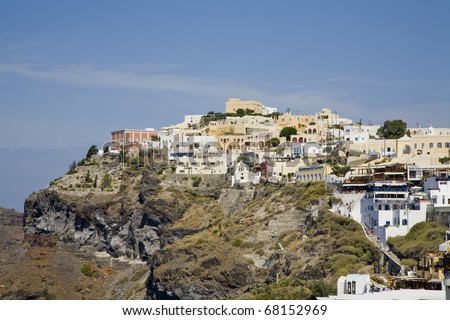 Houses, buildings, and cafes built into the side of the mountain in Santorini Greece - stock photo