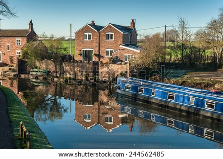Houses by a canal with narrow boats in Anderton, Cheshire uk. - stock photo
