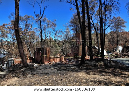 Houses caught up in bushfires have been razed to the ground, while others were spared. - stock photo
