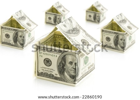 houses from dollars on white isolated background - stock photo