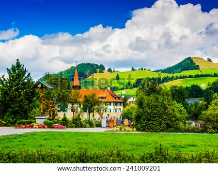 Houses in a little swiss town with clouds and blue sky in background, Switzerland. - stock photo