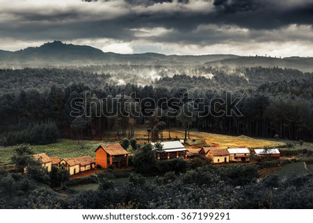 Houses in deforestation area with smoke over the forest's remains. Slash and burn type of agriculture of Madagascar - stock photo