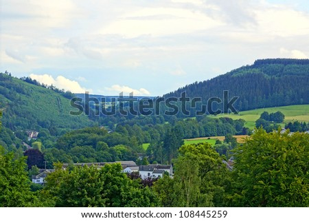 Houses in the green hills of the ardennes - stock photo