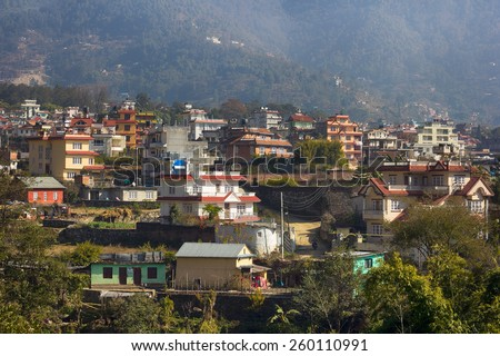 houses in valley in front of mountain in Nepal - stock photo