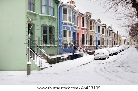 houses in winter snow, victorian or edwardian english architecture in Brighton. Typical street with bright exterior - stock photo