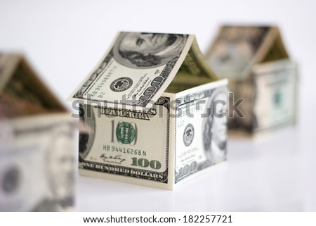 Houses made from dollar banknotes. Shallow depth of field. - stock photo
