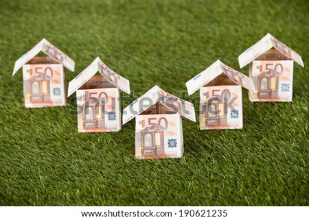 Houses made of euro notes on grassy land - stock photo