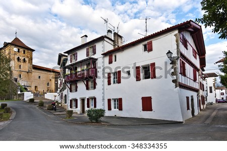Houses of Espelette village in French Basque country, Saint Etienne church is at left. Province of Labourd, Atlantic Pyrenees, Aquitaine, France  - stock photo