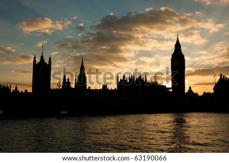Houses of parliament and Big Ben in silhouette at sunset with moody sky - stock photo