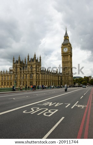 Houses of Parliament and Big Ben with detail of bus lane and moody sky - stock photo