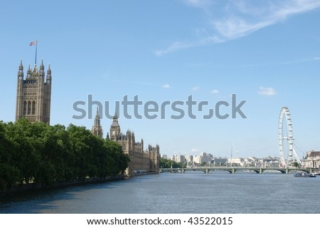 Houses of Parliament and the London Eye seen from the River Thames - stock photo