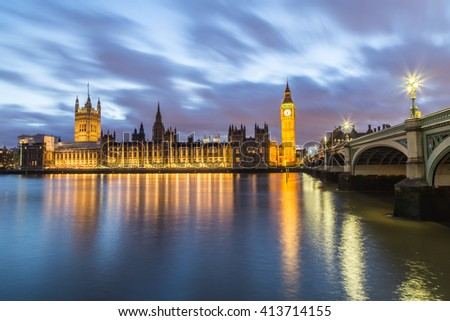 Houses of Parliament from across the River Thames at dusk. Part of Westminster Bridge can be seen. - stock photo
