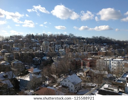 Houses on a hillside beneath blue sky and clouds, suburban Boston - stock photo