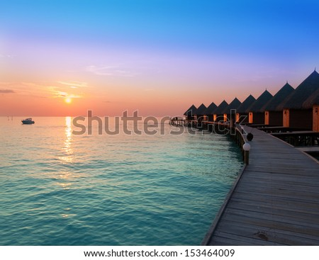 houses on piles on water at the time sunset. - stock photo