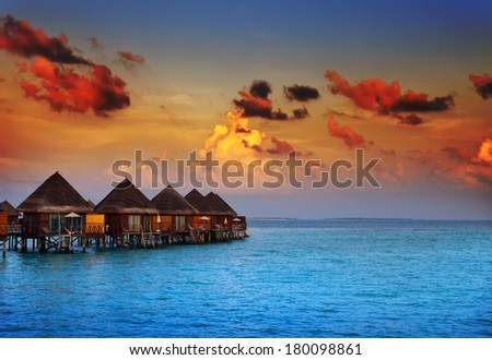 houses on piles on water at the time sunset - stock photo