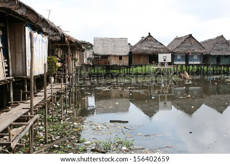 Houses on stilts rise above the polluted water in Belen, Iquitos, Peru. Thousands of people live here in extreme poverty without clean water or sanitation. - stock photo