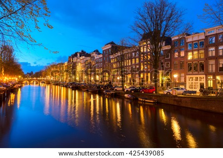 Houses over canal with lights and reflections at night, Amstardam, Netherlands