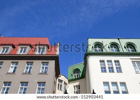 houses with red and green metal roofs over blue sky - stock photo