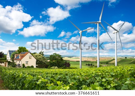 Houses with solar panels on roof and wind turbines nearby. Summer landscape with green vineyard. Eco energy concept.
