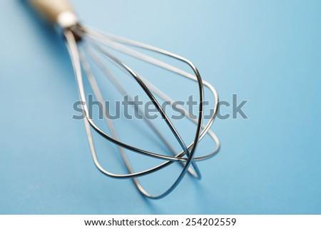 Housewares whisk, isolated on blue background - stock photo