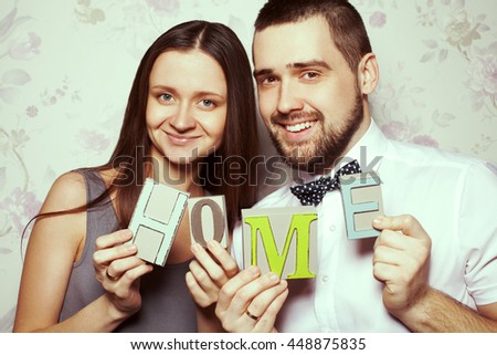 Housewarming party concept. Portrait of funny smiling hipster couple husband and wife in trendy clothes holding letters HOME together. Casual, vintage style. Close up. Studio shot